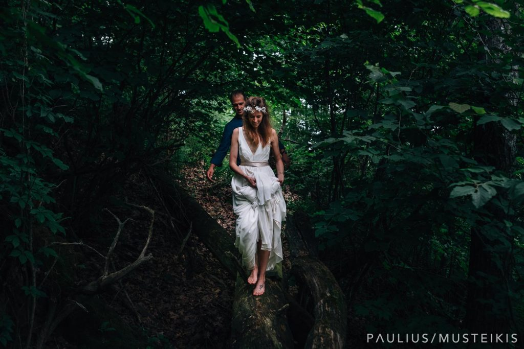 bride and groom are walking barefoot in the woods near Wisconsin river