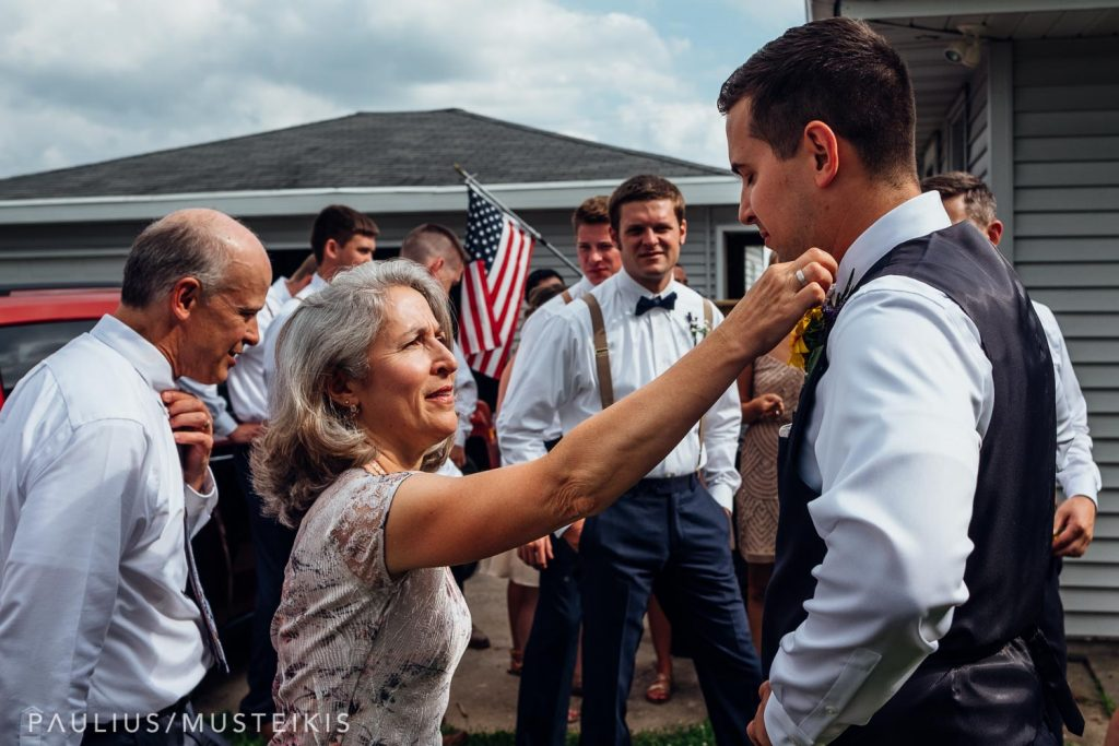 mother of the groom is fixing grooms tie before Wisconsin family farm wedding ceremony