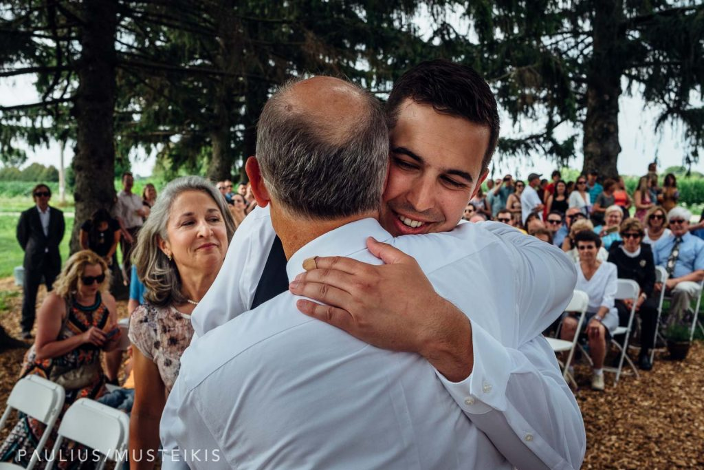 groom hugging his father and smiling during Wisconsin family farm wedding ceremony