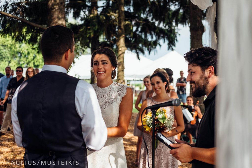 bride and groom holding hands and smiling during wedding ceremony