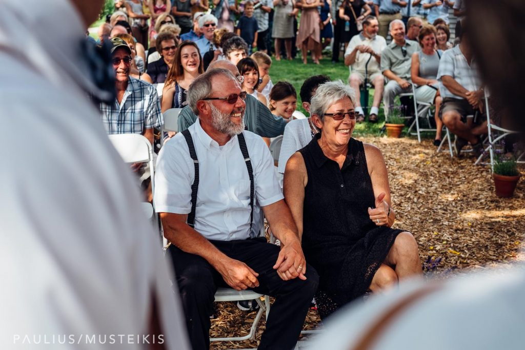 parents of the bride holding hands and laughing Wisconsin family farm wedding ceremony