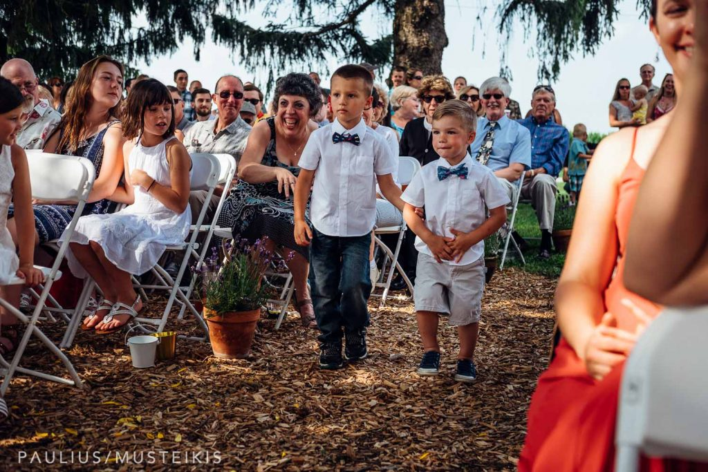 two ring bearers walking down the isle at the Wisconsin family farm wedding ceremony
