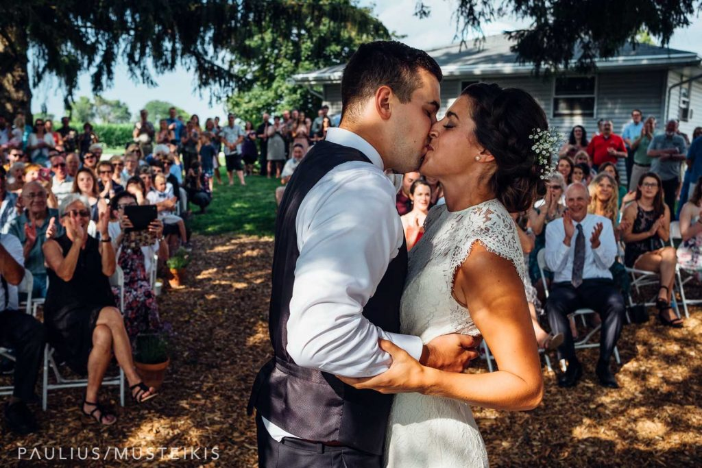bride and groom kises after excaning rings and reading wows during Wisconsin family farm wedding ceremony