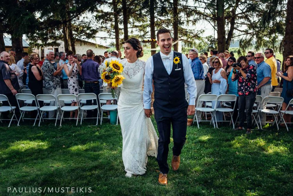 bride and groom are walking away after Wisconsin family farm wedding ceremony