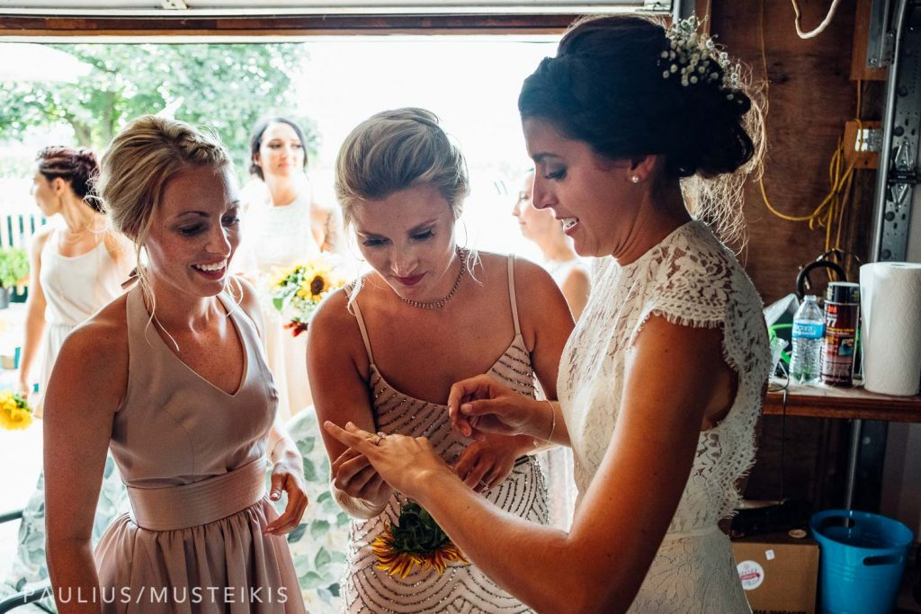 bride and bridesmaids examining bride's wedding ring