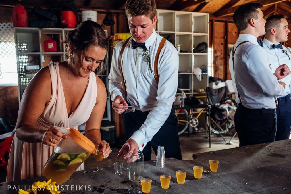 bridesmaid and groomsman pouring shot glasses for a toast