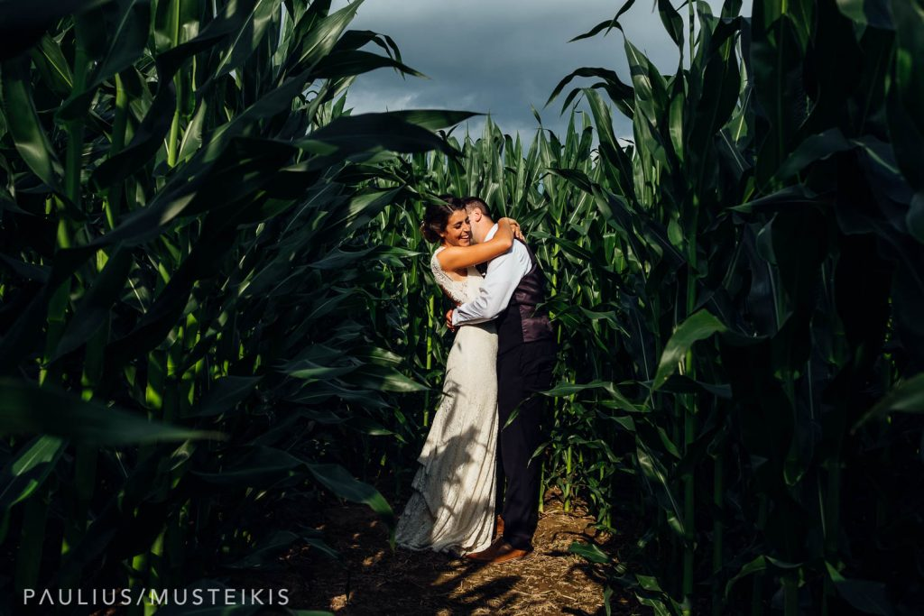 bride and groom hugging in family farm cornfield