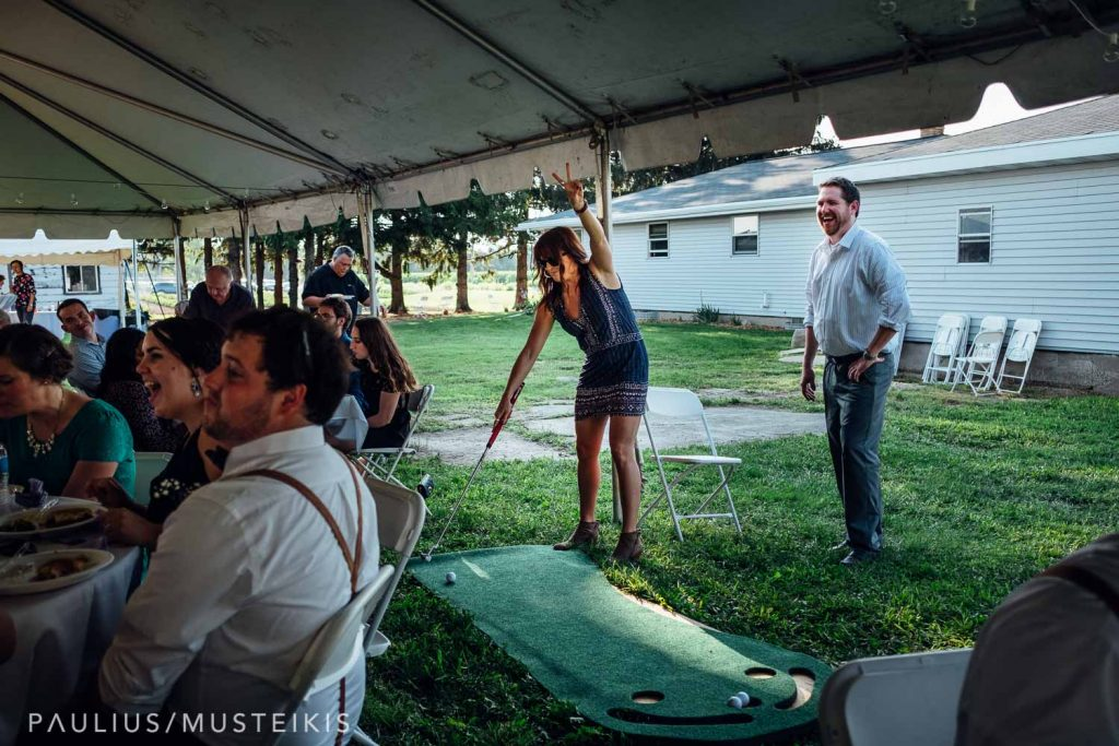wedding guests are playing mini golf at the wedding reception in family farm