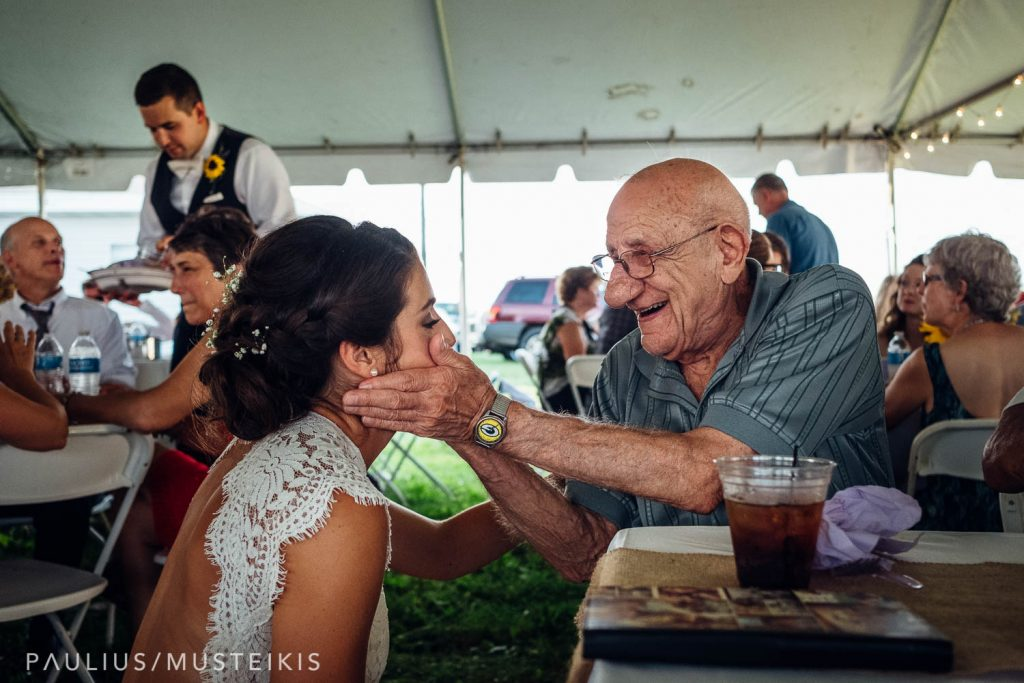 bride and her grandfather are hugging during wedding reception at the family farm