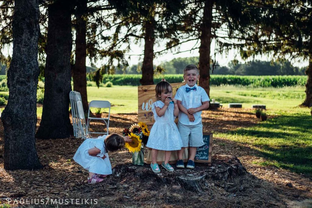 three kids standing and laughing next to wedding ceremony decorations