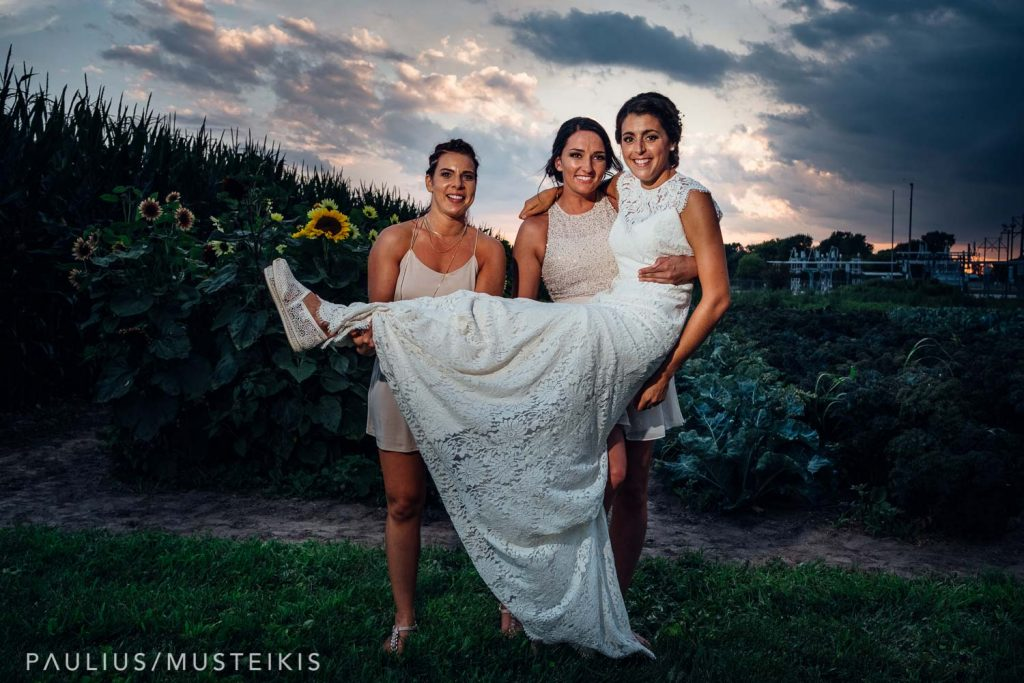 two bridesmaids holding bride in their arms