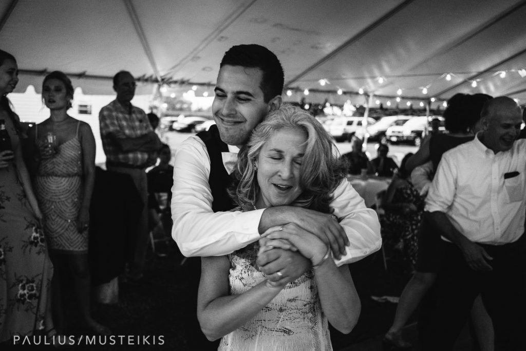 groom embraces his mom during the mother-son dance
