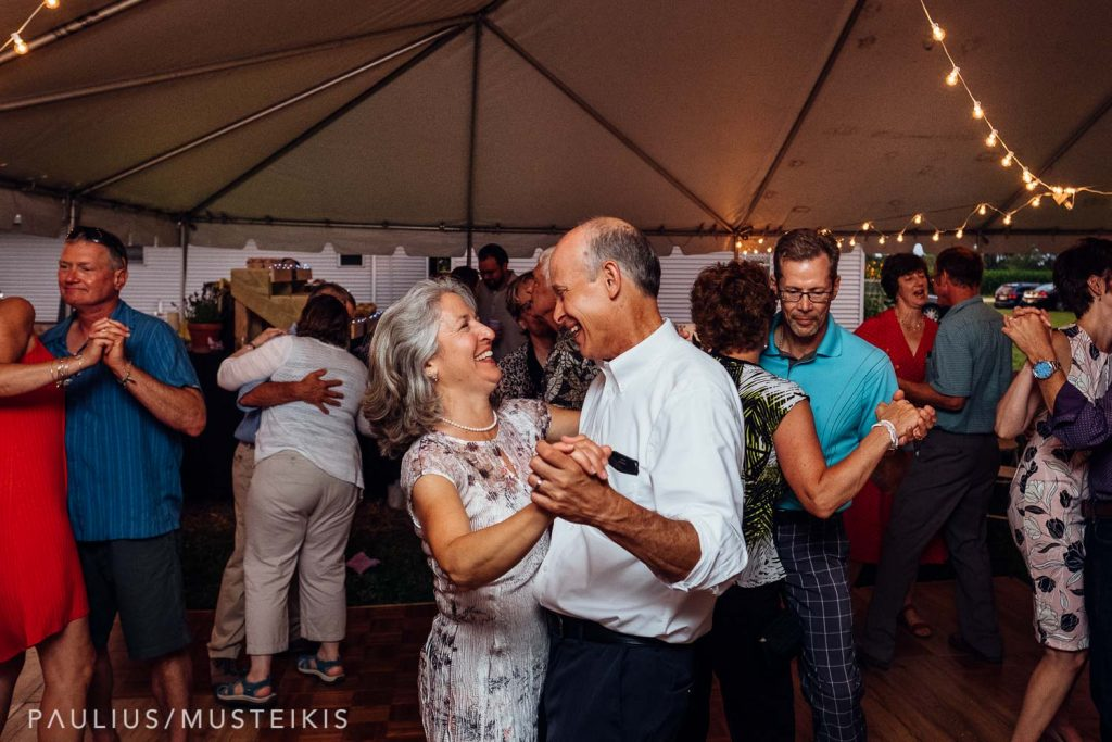 wedding guests dancing and laughing on the dancefloor in the Wisconsin family farm wedding