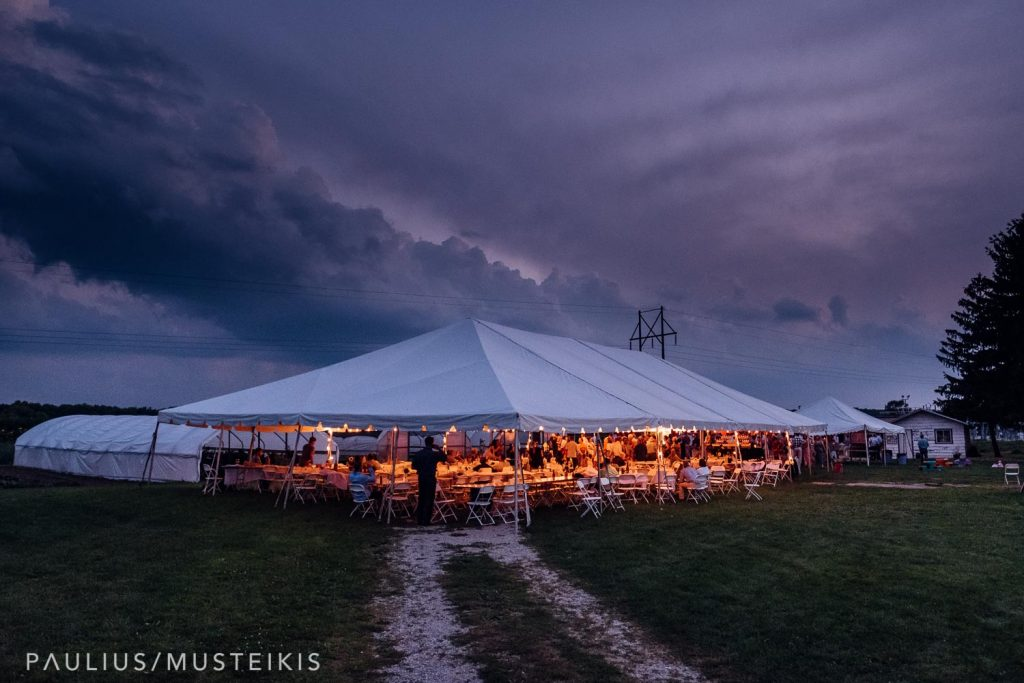 wedding reception tent with stormy evening summer sky with intense clouds and beautiful light at the Wisconsin family farm wedding
