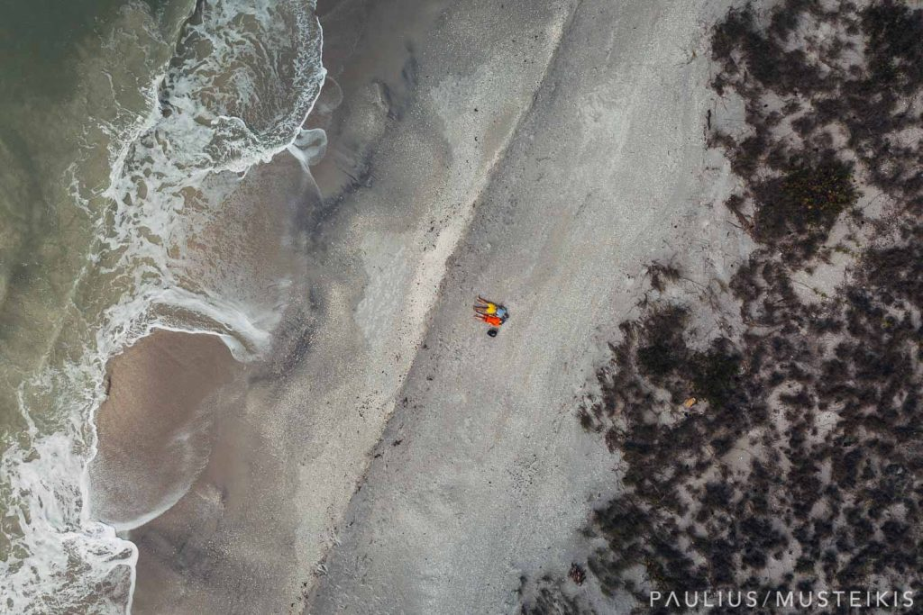 aerial image from above of wedding photographer that gives back with his son laying in the beach