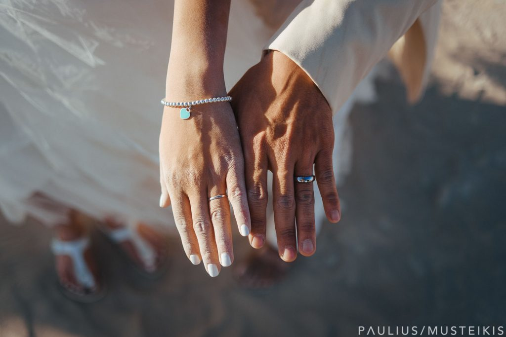 dusty bride's and groom's hands with wedding rings on fingers