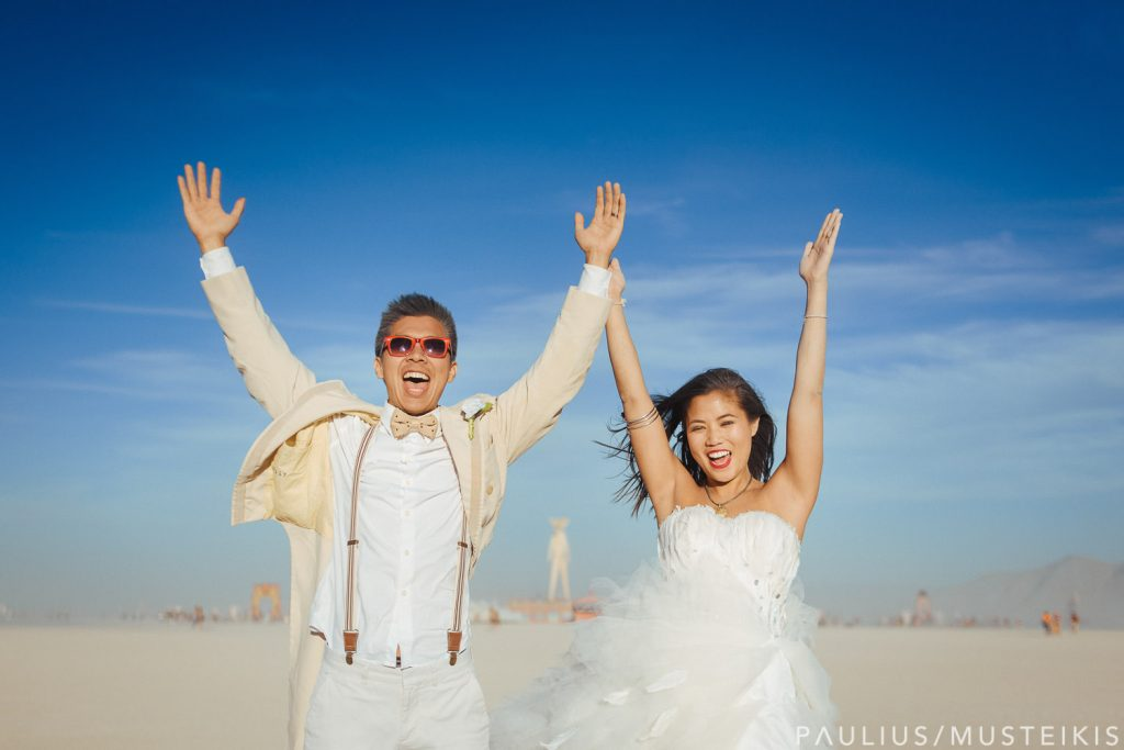 bride and groom raising their hands and shouting after their Burning Man wedding ceremony