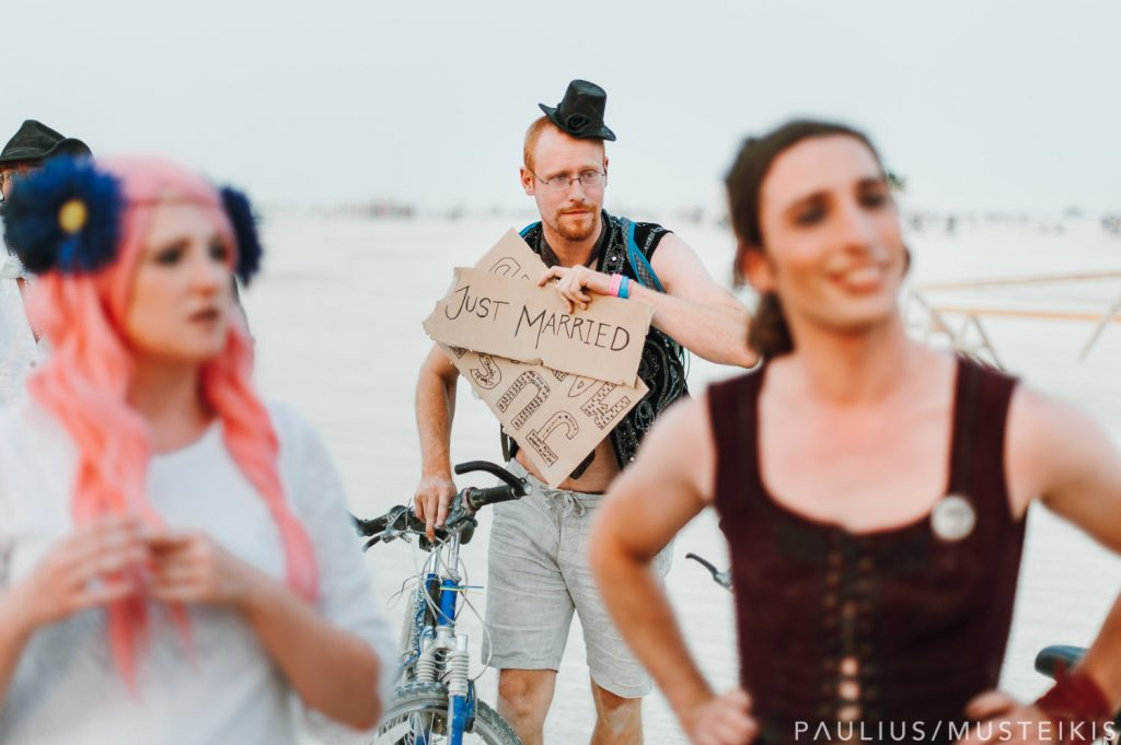 "man holding ""just married"" sign after the Burning Man wedding ceremony"