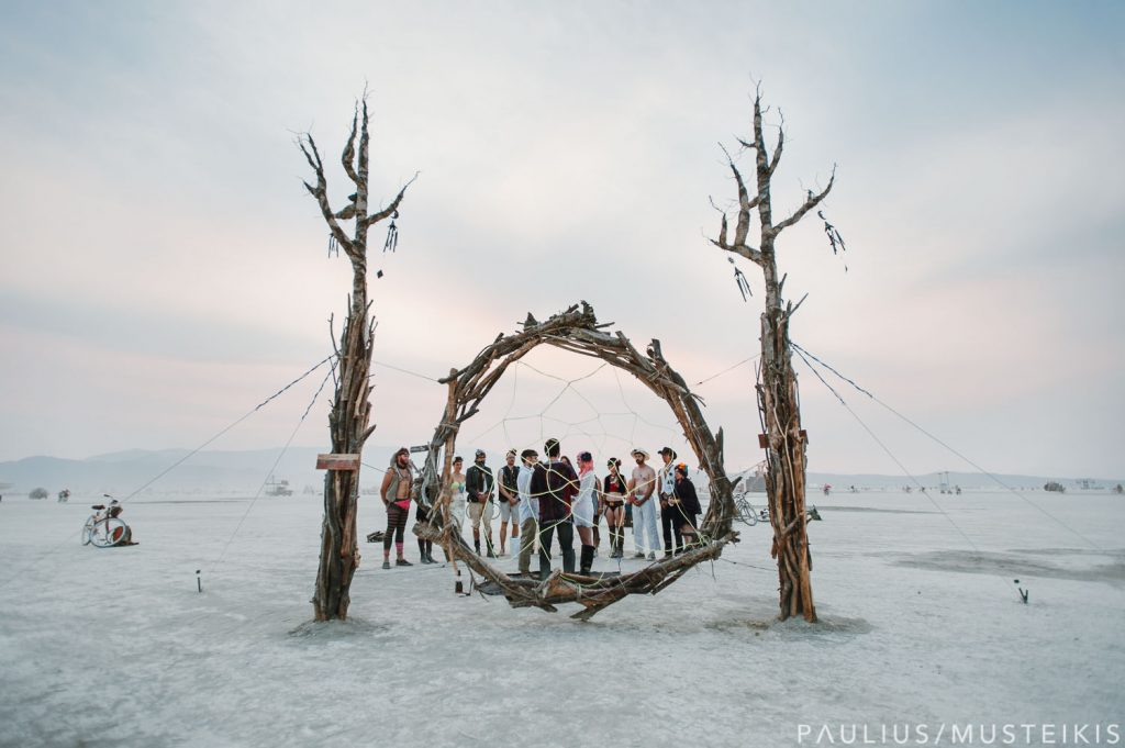 group of people gathered for a wedding ceremony near art installation in Burning Man