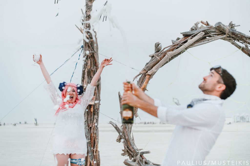 groom is opening and spilling champagne bottle while bride is laughing