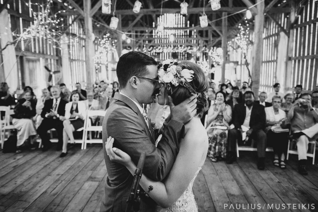 bride and groom exchanging their first kiss with wedding guest in the background