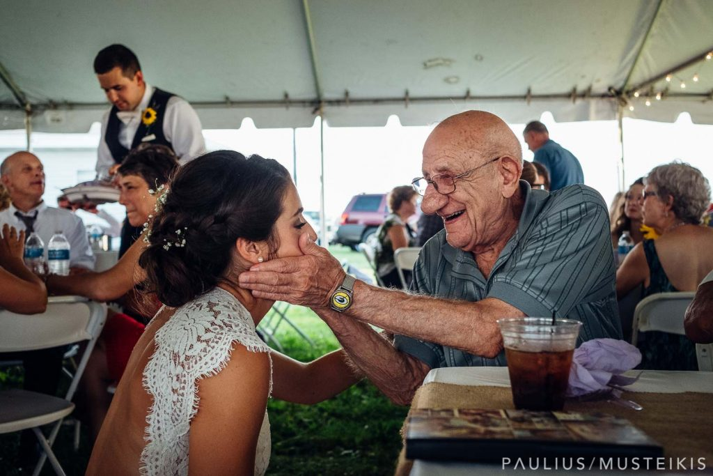 bride is tearing up while grandfather holding her cheeks during family farm wedding