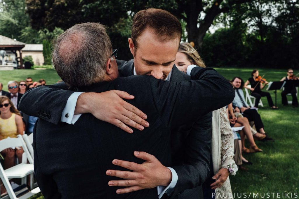 groom hugging and his dad during wedding ceremony on a shore of lake Mendota, Madison Wisconsin