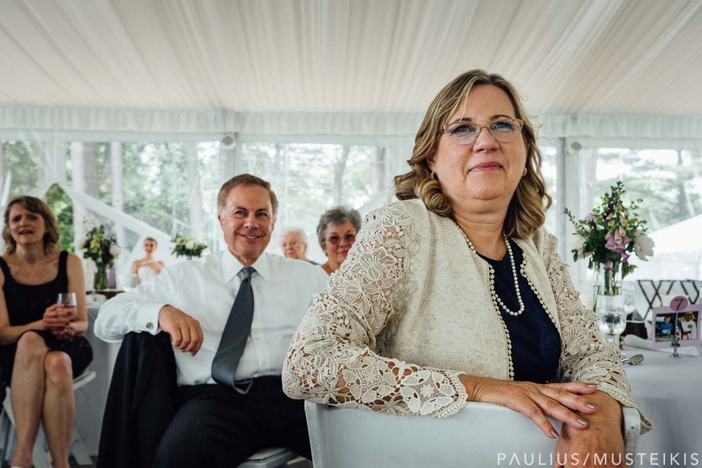 parents of the groom are smiling while listening to wedding speeches