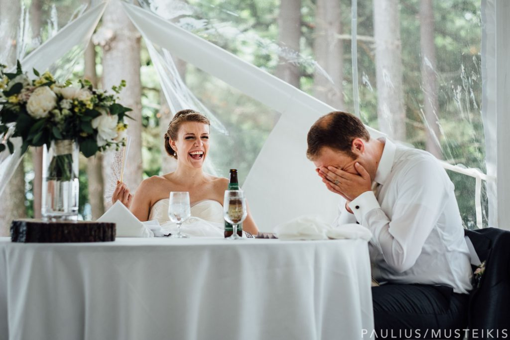 groom and groom laughing during wedding speeches in Bishops bay country club outdoor tent