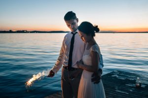 bride and groom with sparklers standing on the dock at James Madison park wedding