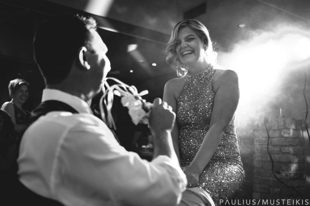 bride is laughing while looking at the groom during wedding reception