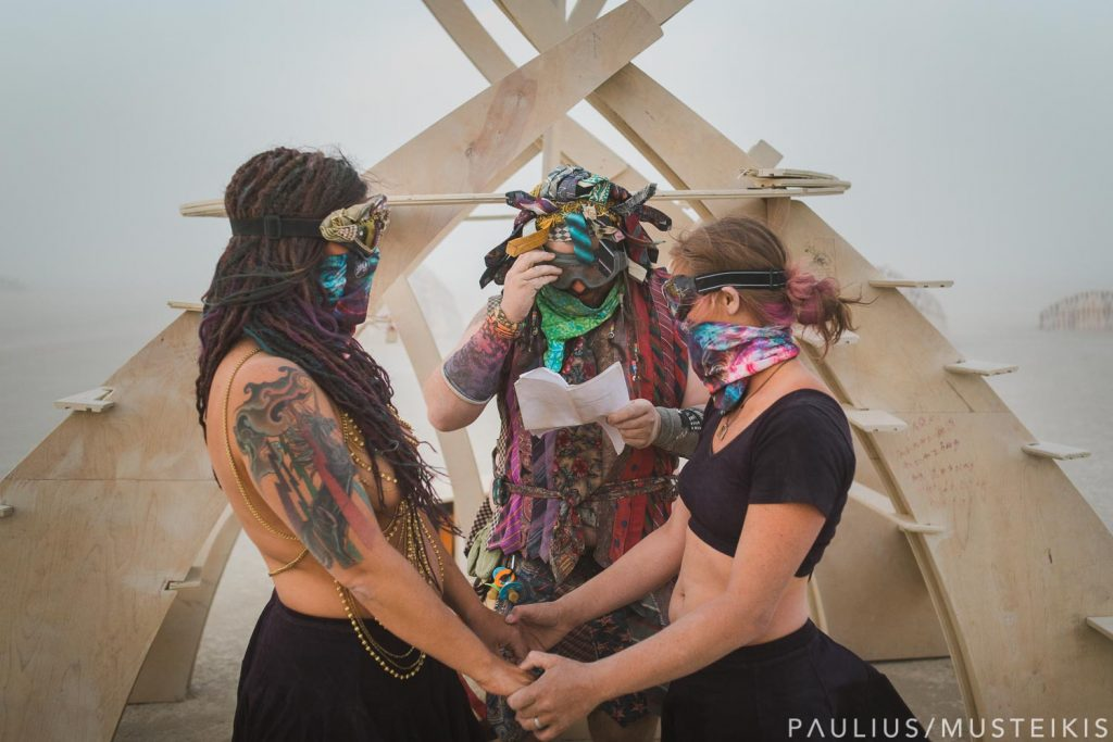 lesbian couple and officiant during the same-sex wedding ceremony in the desert