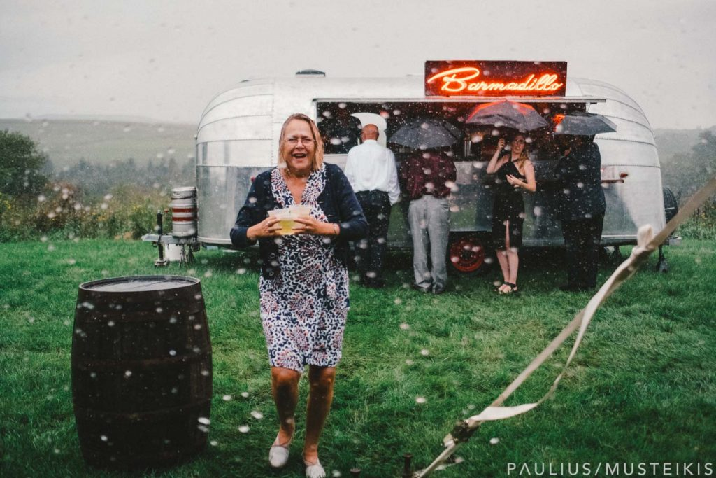 wedding guest at the outdoor bar during heavy rain