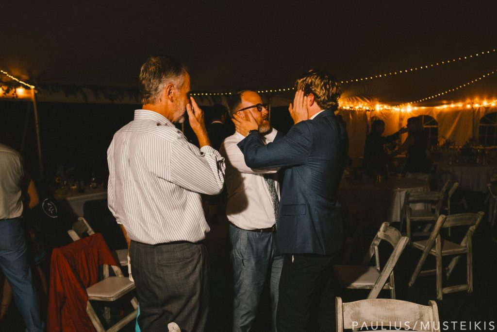 groom interacting with a guest at the Prevailing Winds lodge wedding