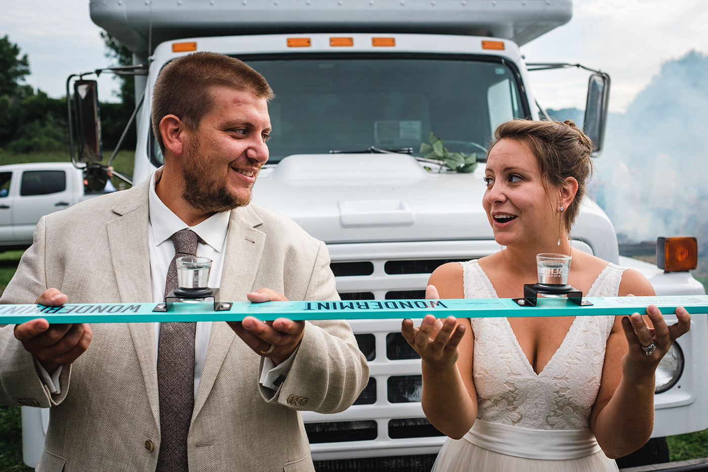 Bride and groom drinking from shot ski during their wedding