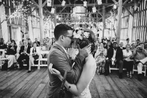 Bride and groom kissing after wedding ceremony in Gatherings On The Ridge barn