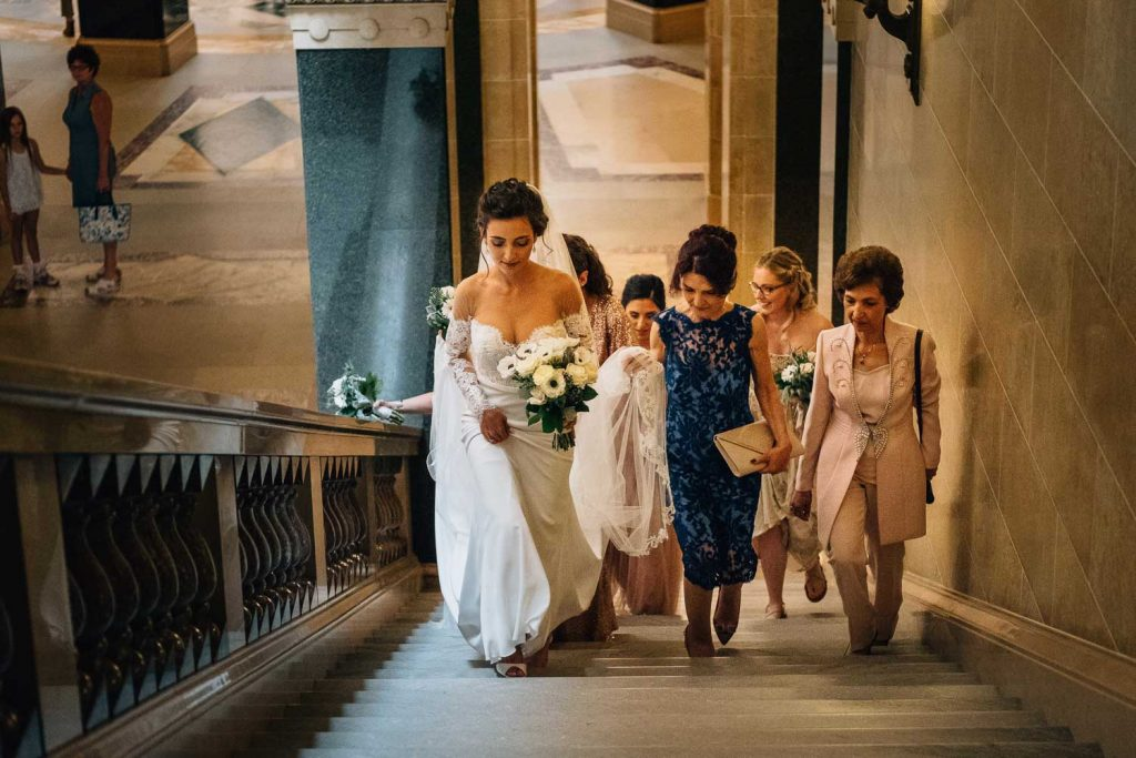 bride and bridesmaids walking up the stairs before the wedding ceremony