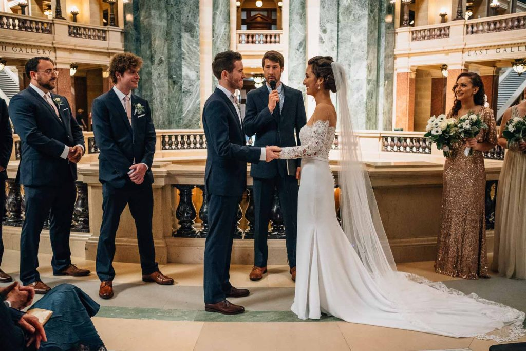bride and groom holding hands during wedding ceremony in Wisconsin State Capitol