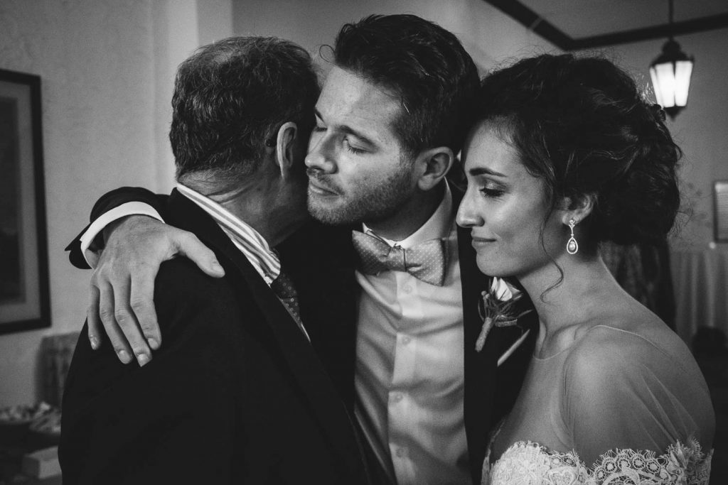 wedding couple hugging a guest at the University Club wedding reception