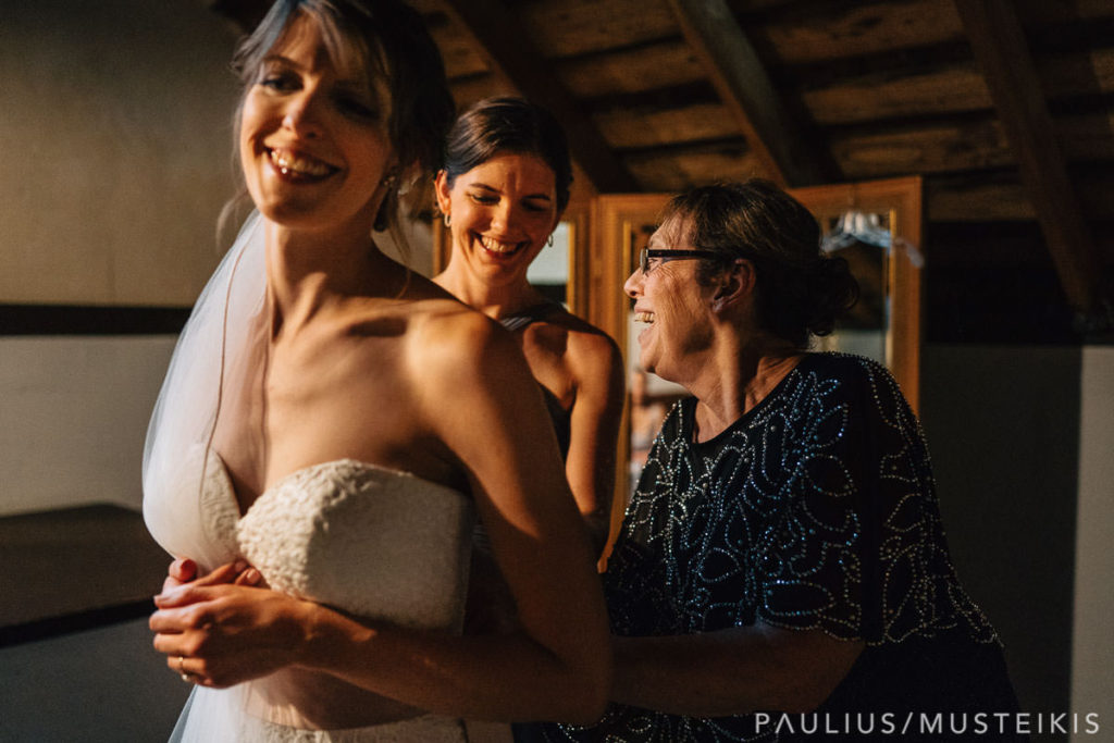 bride's mother and sister bustling wedding dress and smiling